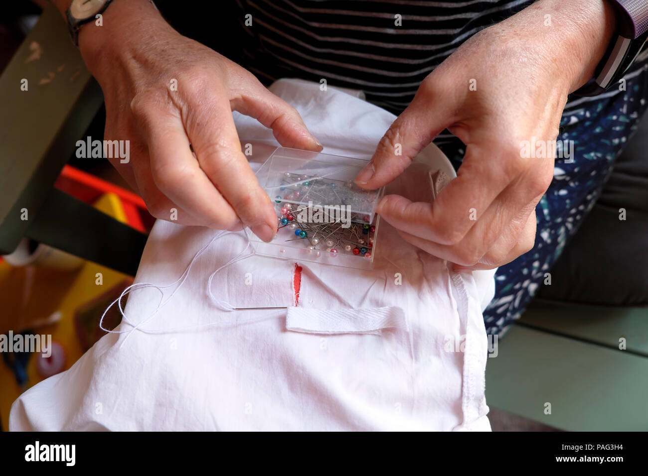 Close-up of an older woman's hands repairing mending a sheet sewing with white cotton tape Wales UK  KATHY DEWITT - Stock Image