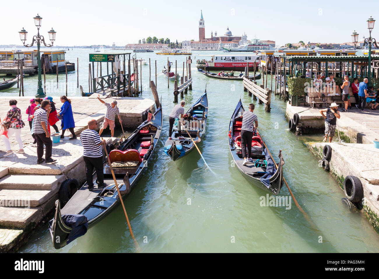 Gondoliers, gondolas offloading passengers, Riva degli Schiavonni, Castello, Venice, Veneto, Italy in Rio del Vin, San Giorgio Maggiore and lagoon beh - Stock Image