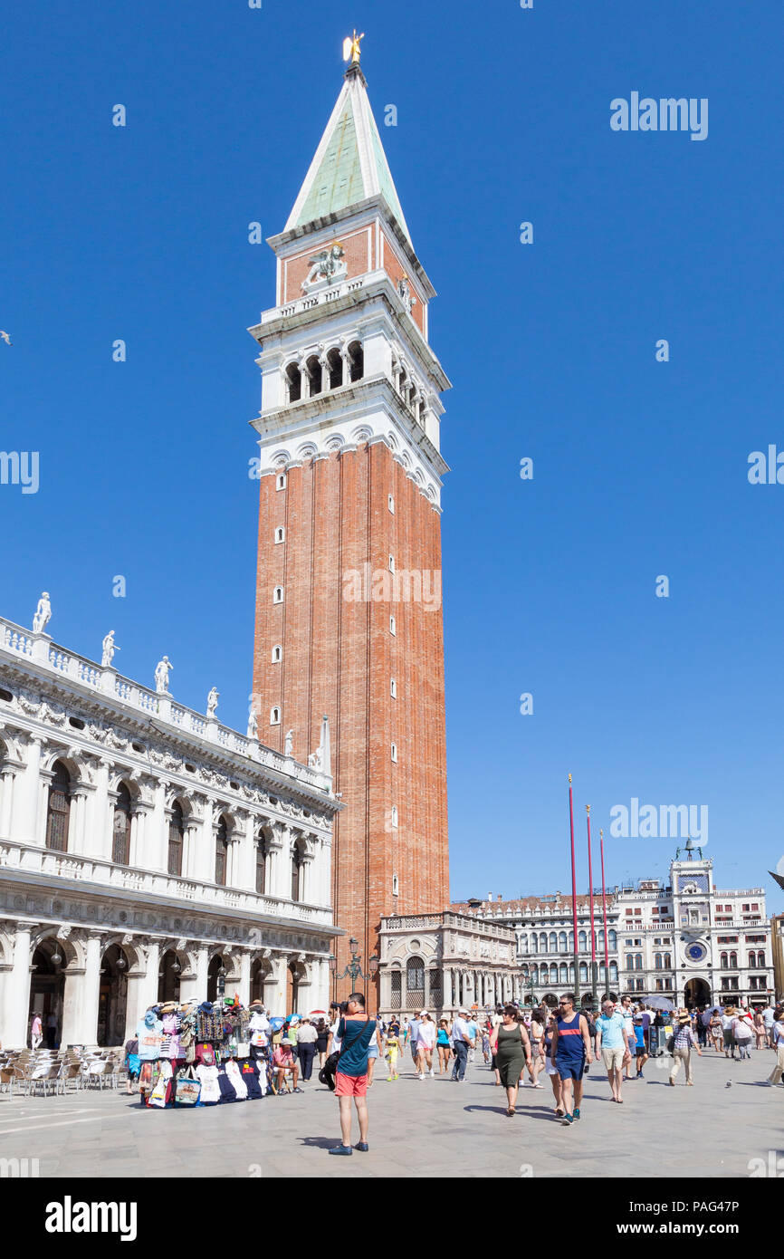 Campanile or bell tower of St Marks Cathedral, Piazza San Marco, San Marco, Venice, Veneto, Italy with tourists against a blue sky - Stock Image