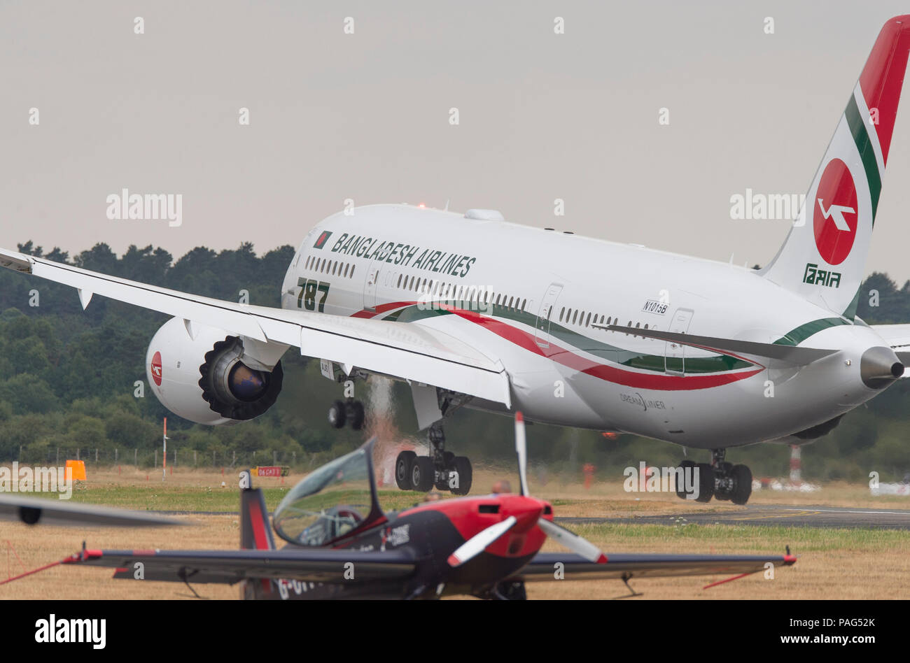 Boeing 787 Dreamliner of Bangladesh Airlines leaves Farnborough at the end of the 2018 Trade Airshow, with a small Blades aircraft in the foreground. - Stock Image