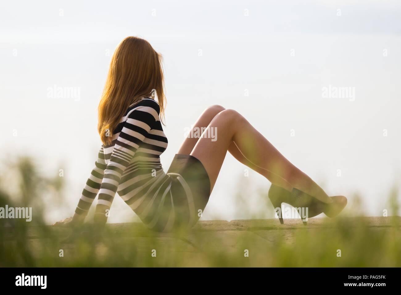 Teen adult teen adolescent sitting on seafront edge looking away legs heels slender fit thin elegant model-released release teenage teenager sleek Stock Photo