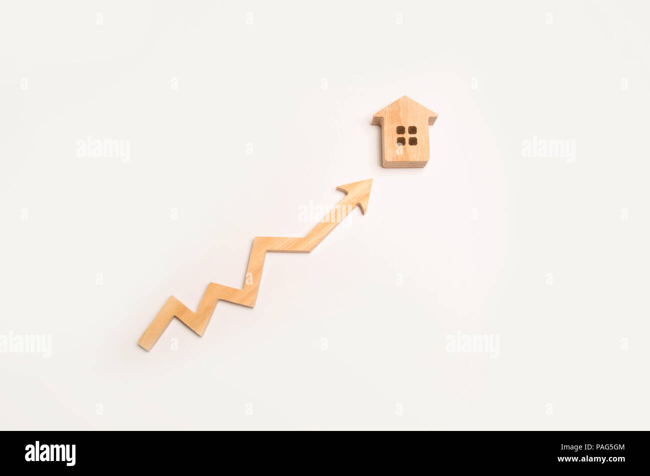 Wooden arrow up arrow points to a wooden house. The concept of revenue growth and cost. Increase the efficiency of business. Improving the quality of  Stock Photo