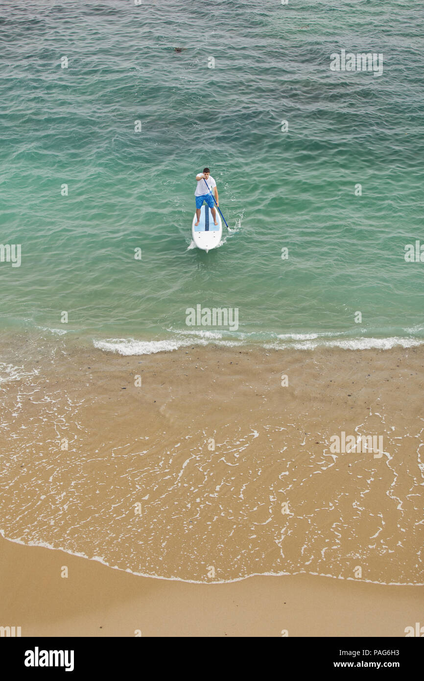 A young man in blue swim trunks and a white t-shirt paddling a paddle board in the clear, blue water of Laguna BEach, California. - Stock Image