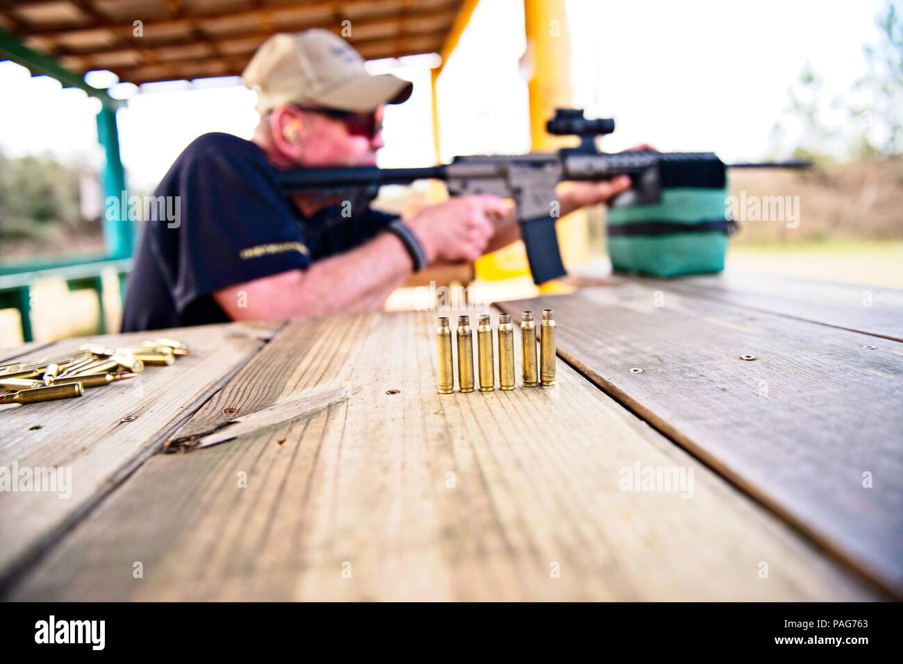 A row of spent rifle cartridges are isolated with a main looking through the scope of a rifle is in the background - Stock Image