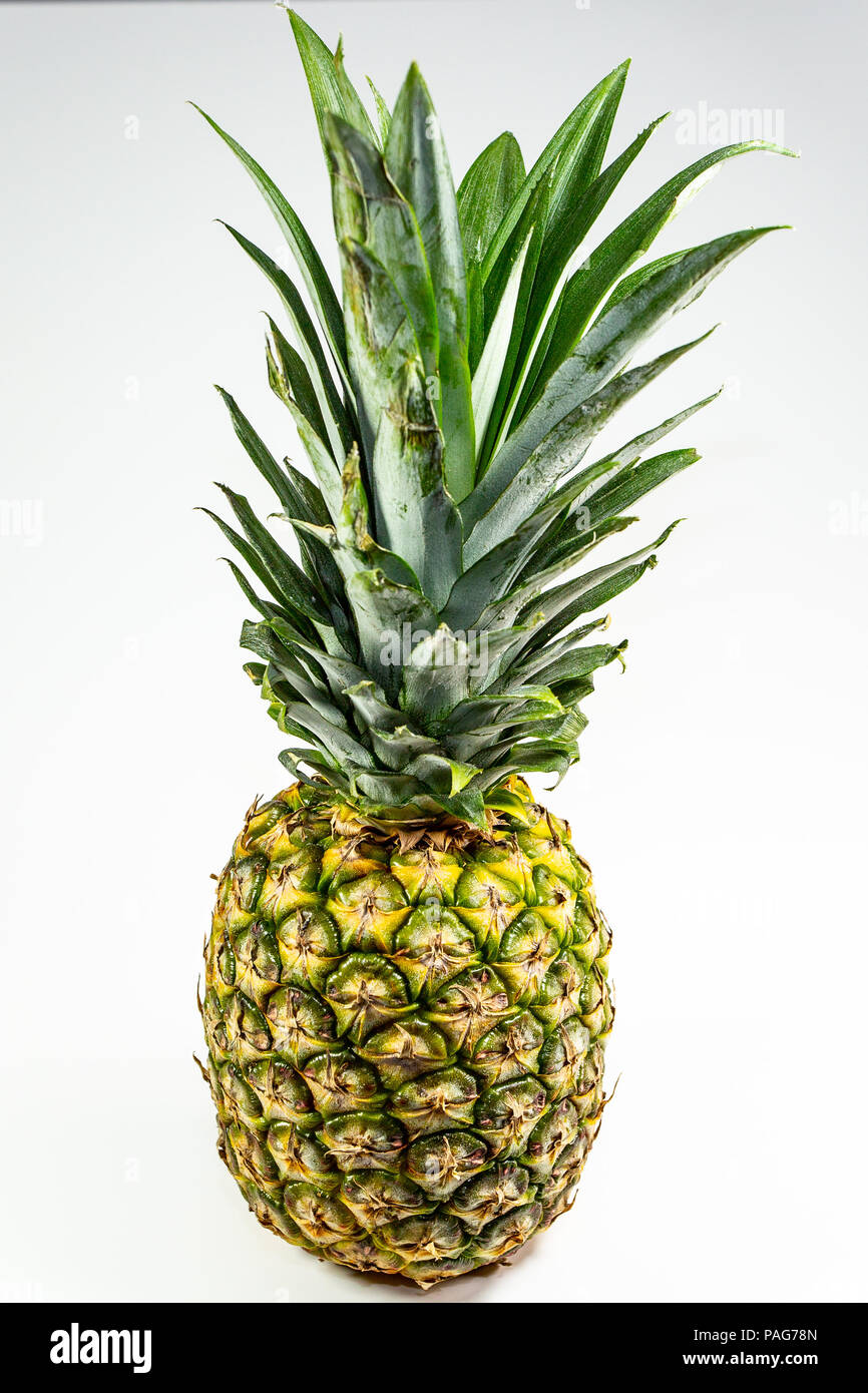 Pineapple on a table waiting for the chef to carve it and serve - Stock Image