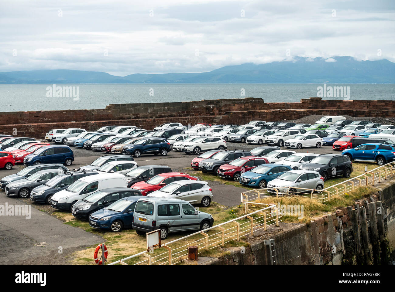 Cars in the car park at Ardrossan Harbour, North Ayshire, with the Isle of Arran (for which Ardrossan is the departure port) in the background. - Stock Image