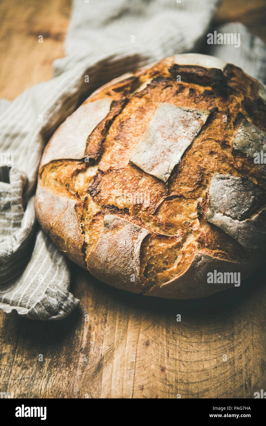Sourdough wheat bread over rustic background, selective focus - Stock Image