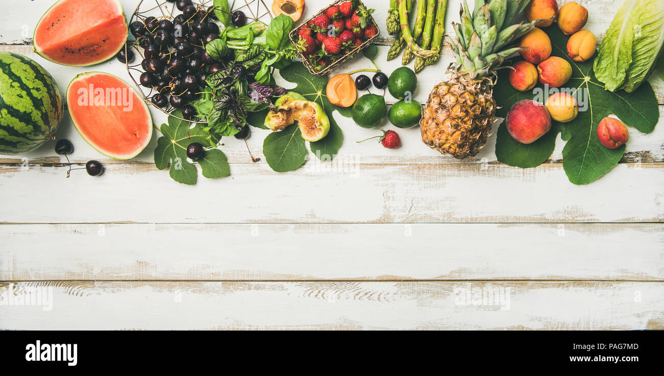 Flat-lay of seasonal fruit, vegetables and greens over wooden background - Stock Image