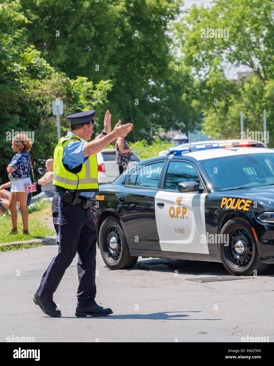 An auxiliary police officer directs traffic on a busy street during an event in Orillia Ontario. - Stock Image
