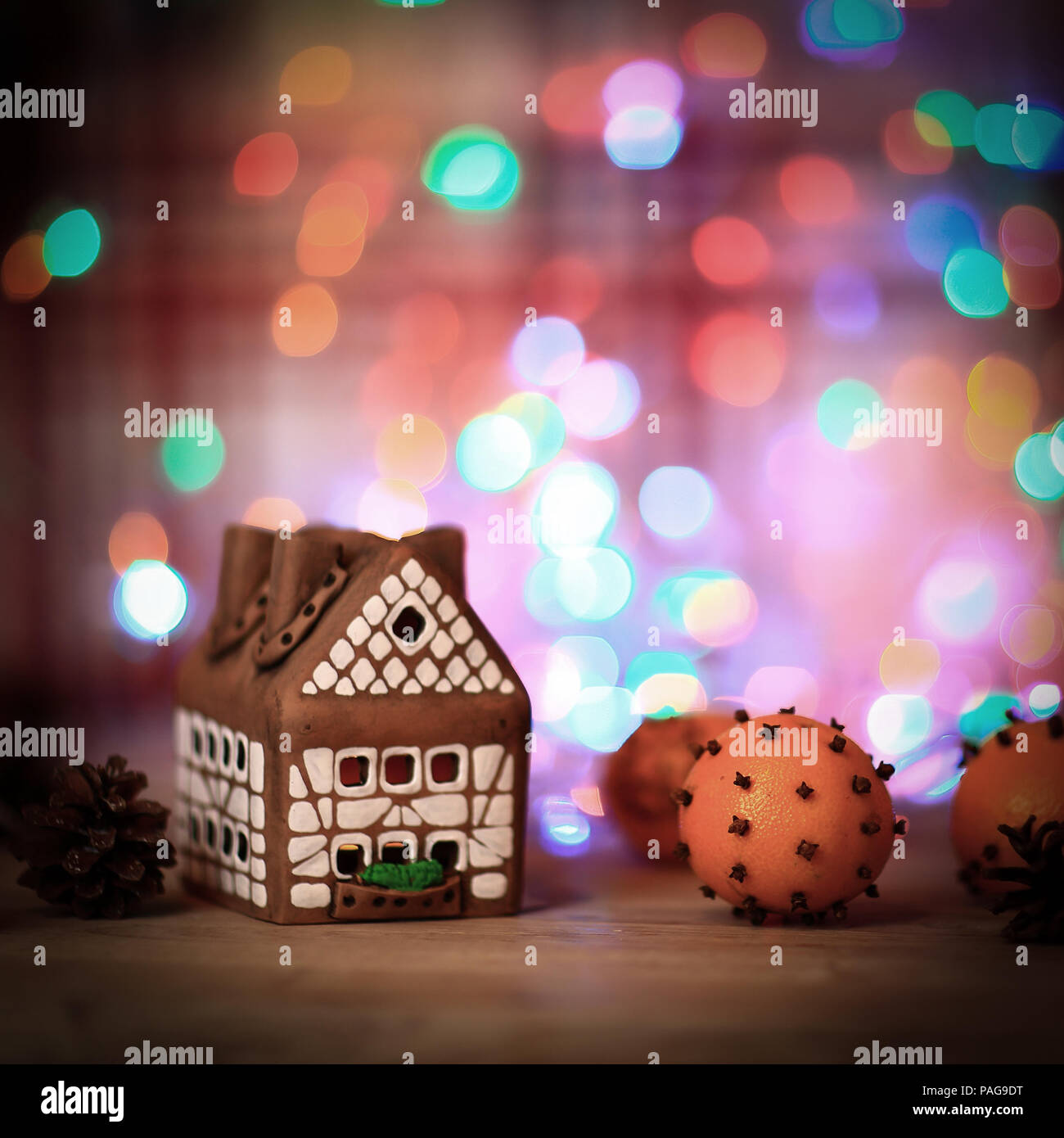 gingerbread house and oranges at the Christmas table - Stock Image