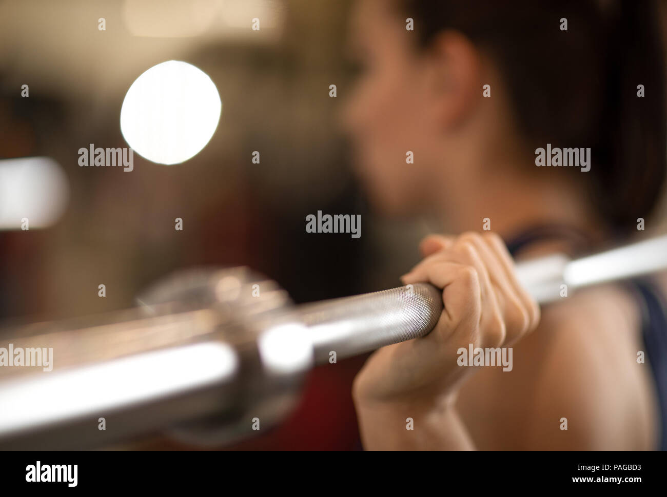 Young woman training with barbell in gym - Stock Image