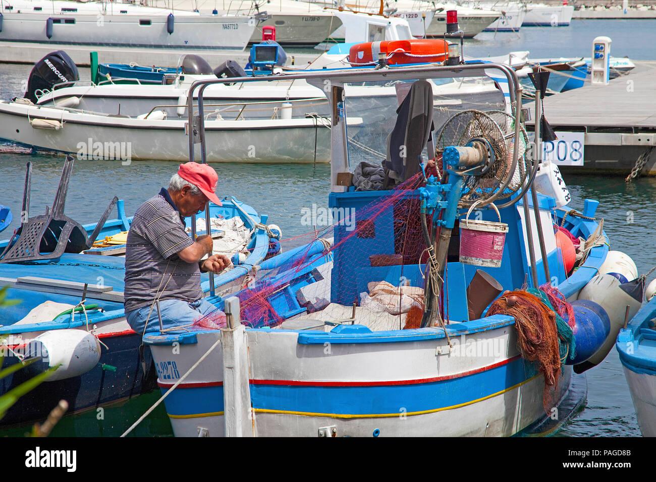 Fisherman on fisherman's boat repairing fishing nets  Marina Grande, Procida island, Gulf of Naples, Italy - Stock Image