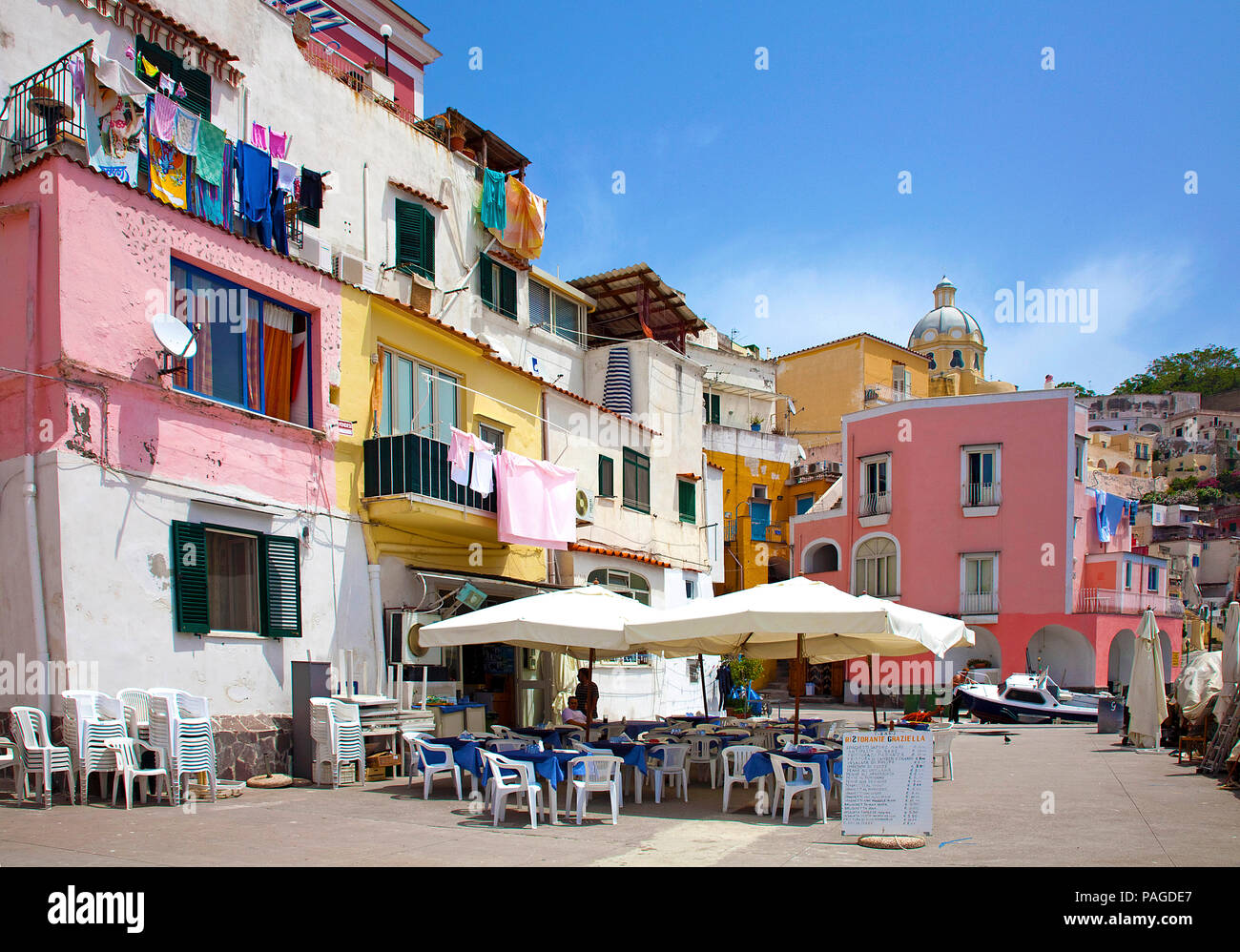 Idyllic harbour restaurant at fishing harbour Marina di Corricella, Procida, Gulf of Naples, Italy - Stock Image
