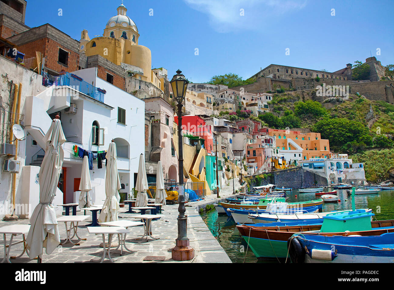 The idyllic fishing village Procida with fishing harbour Marina di Corricella, above the fortress Terra Murata, a former prison, Gulf of Naples, Italy - Stock Image