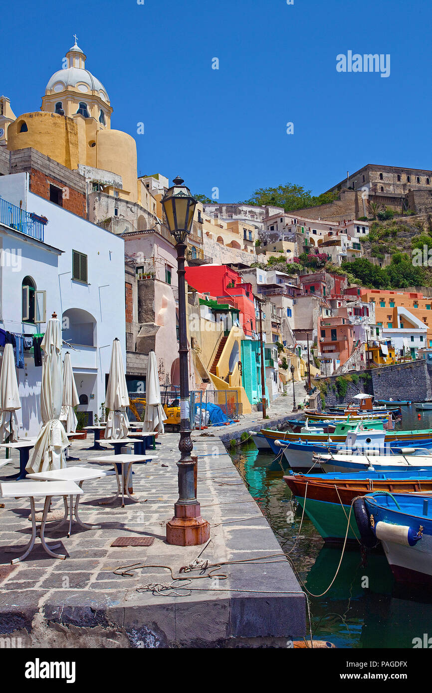 The idyllic fishing village Procida with fishing harbour Marina di Corricella and above fortress Terra Murata, a former prison, Gulf of Naples, Italy - Stock Image