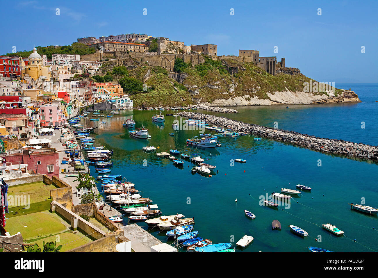 The fishing village Procida with fishing harbour Marina di Corricella and fortress Terra Murata, a former prison, Gulf of Naples, Italy - Stock Image