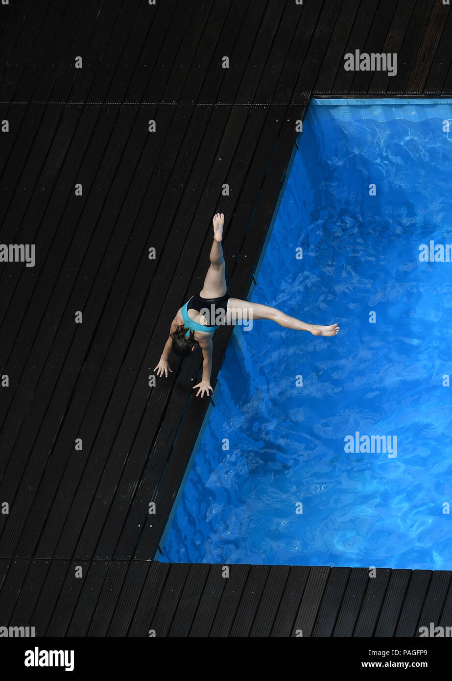 Essen, Germany. 22nd July, 2018. A girl jumps into the works swimming pool on the premises of the coking plant of the Zollverein Coal Mine Industrial Complex (Zeche Zollverein). The Frankfurt artists Dirk Paschke and Daniel Milohnic created the work swimming pool in 2001 in the course of the art project 'Zeitgenoessische Kunst und Kritik' (lit. contemporary art and criticism). Credit: Ina Fassbender/dpa - ATTENTION: editorial use only in connection with the latest coverage and only if the credit mentioned above is referenced in full/dpa/Alamy Live News - Stock Image