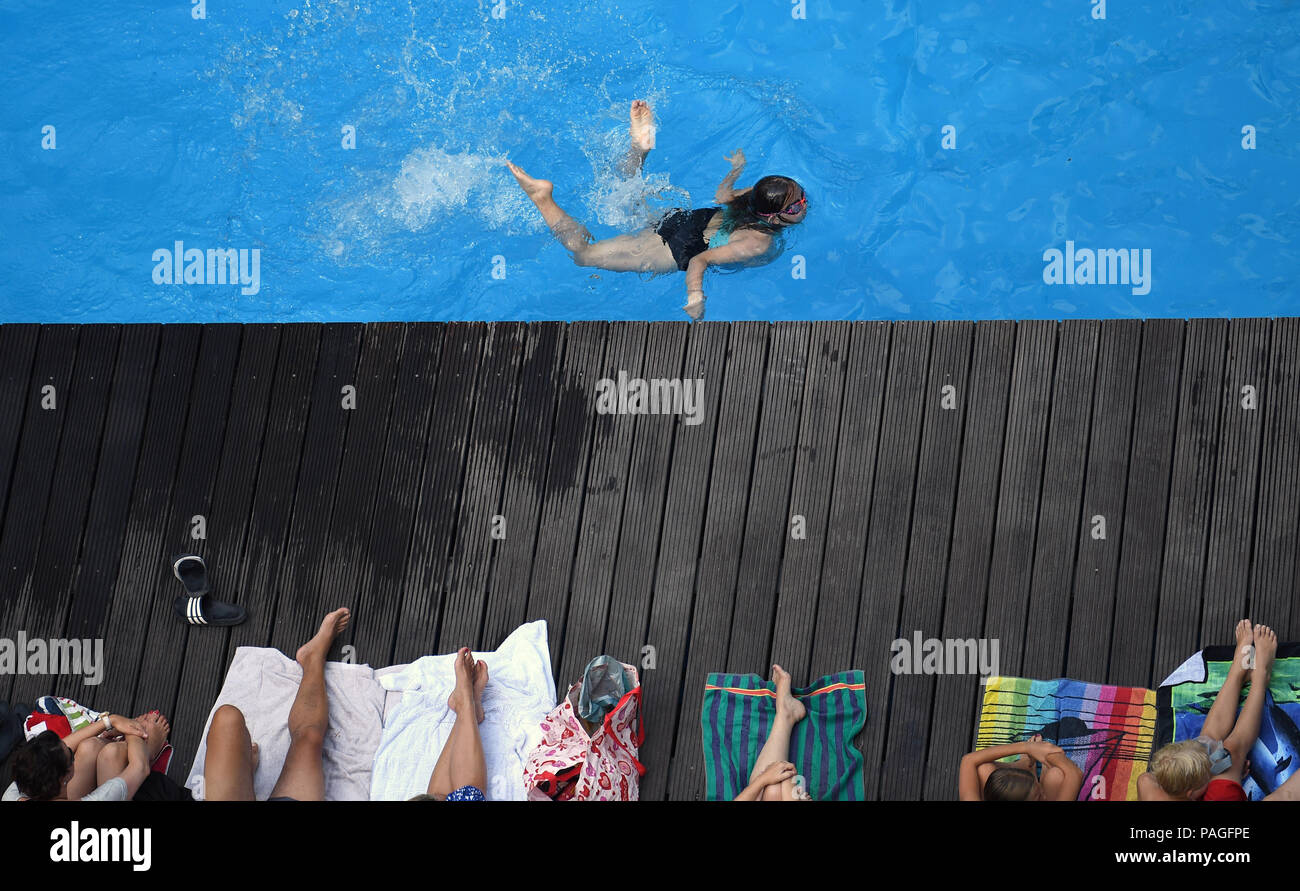 Essen, Germany. 22nd July, 2018. A girl swims past bathers in the works swimming pool on the premises of the coking plant of the Zollverein Coal Mine Industrial Complex (Zeche Zollverein). The Frankfurt artists Dirk Paschke and Daniel Milohnic created the work swimming pool in 2001 in the course of the art project 'Zeitgenoessische Kunst und Kritik' (lit. contemporary art and criticism). Credit: Ina Fassbender/dpa - ATTENTION: editorial use only in connection with the latest coverage and only if the credit mentioned above is referenced in full/dpa/Alamy Live News - Stock Image
