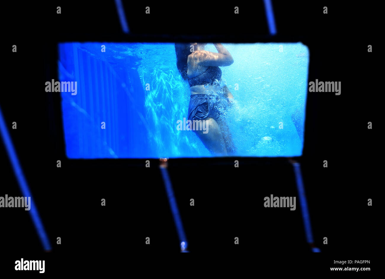 22 July 2018, Germany, Essen: A girl jumps into the works swimming pool on the premises of the coking plant of the Zollverein Coal Mine Industrial Complex (Zeche Zollverein) and can be seen through a window in the pool. The Frankfurt artists Dirk Paschke and Daniel Milohnic created the work swimming pool in 2001 in the course of the art project 'Zeitgenoessische Kunst und Kritik' (lit. contemporary art and criticism). Photo: Ina Fassbender/dpa - ATTENTION: editorial use only in connection with the latest coverage and only if the credit mentioned above is referenced in full - Stock Image