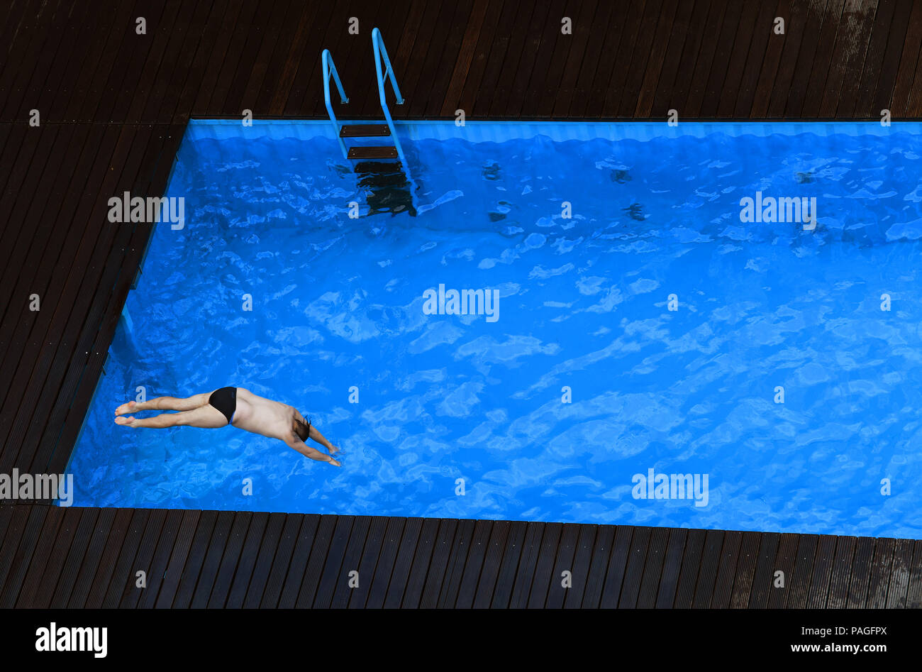 Essen, Germany. 22nd July, 2018. A man jumps into the works swimming pool on the premises of the coking plant of the Zollverein Coal Mine Industrial Complex (Zeche Zollverein). The Frankfurt artists Dirk Paschke and Daniel Milohnic created the work swimming pool in 2001 in the course of the art project 'Zeitgenoessische Kunst und Kritik' (lit. contemporary art and criticism). Credit: Ina Fassbender/dpa - ATTENTION: editorial use only in connection with the latest coverage and only if the credit mentioned above is referenced in full/dpa/Alamy Live News - Stock Image