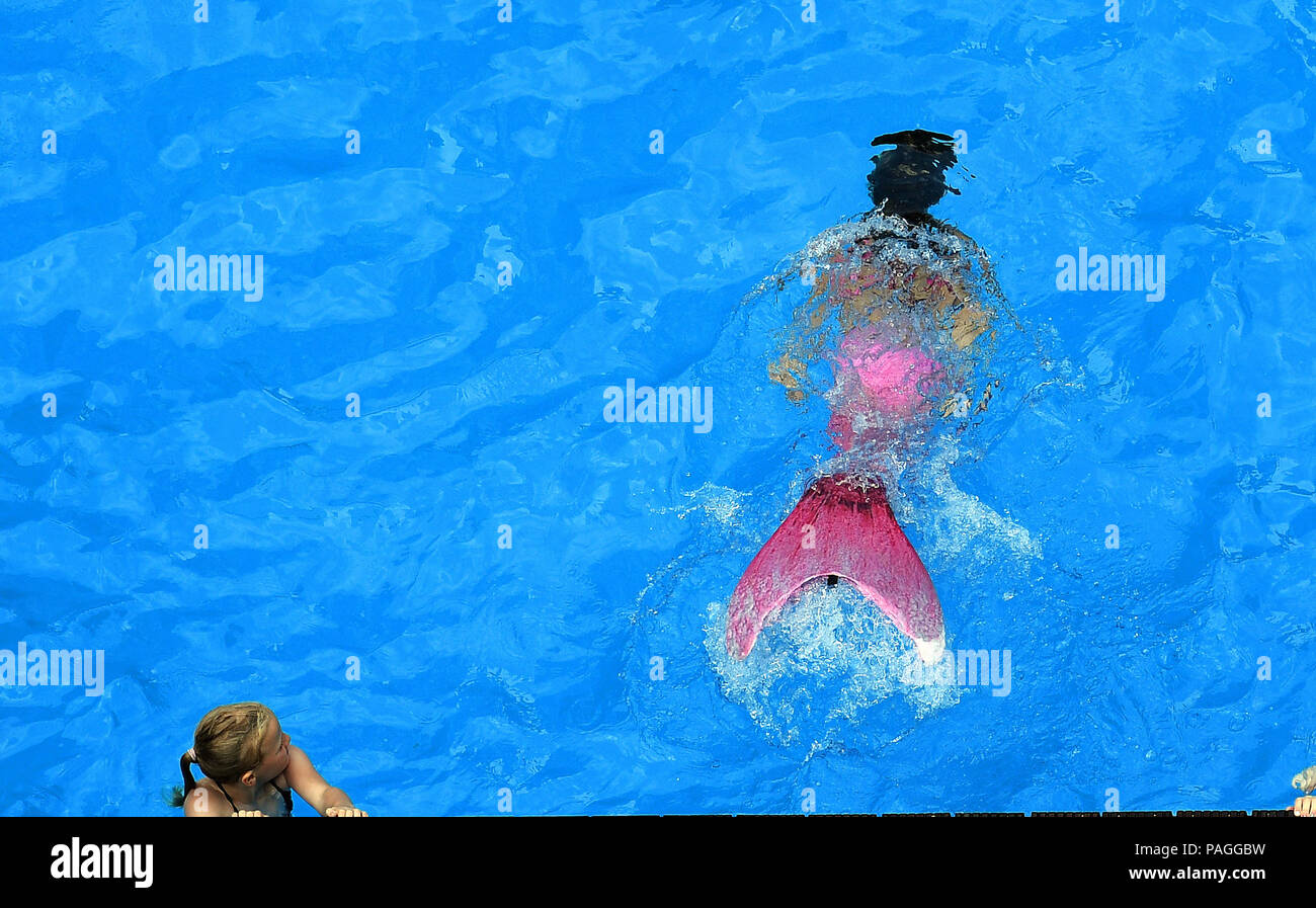 Essen, Germany. 22nd July, 2018. A girl with a mermaid fin swims in the works swimming pool on the premises of the coking plant of the Zollverein Coal Mine Industrial Complex (Zeche Zollverein). The Frankfurt artists Dirk Paschke and Daniel Milohnic created the work swimming pool in 2001 in the course of the art project 'Zeitgenoessische Kunst und Kritik' (lit. contemporary art and criticism). Credit: Ina Fassbender/dpa - ATTENTION: editorial use only in connection with the latest coverage and only if the credit mentioned above is referenced in full/dpa/Alamy Live News - Stock Image