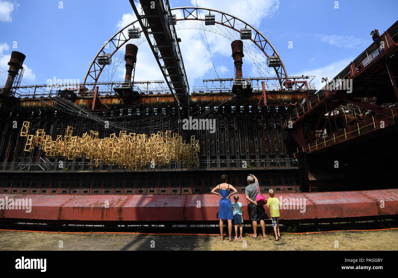 Essen, Germany. 22nd July, 2018. A family takes a look at the sun wheel on the premises of the Zollverein Coal Mine Industrial Complex (Zeche Zollverein). The Frankfurt artists Dirk Paschke and Daniel Milohnic created the work swimming pool in 2001 in the course of the art project 'Zeitgenoessische Kunst und Kritik' (lit. contemporary art and criticism). Credit: Ina Fassbender/dpa/Alamy Live News - Stock Image