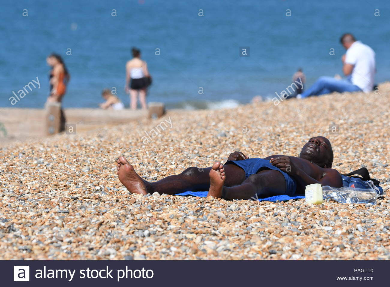 Brighton, East Sussex, UK. Monday 23rd July 2018. A man lays on the beach on another hot and sunny morning in Brighton. The temperature is expected to reach 24C today, reaching into the 30s by midweek. Credit: Geoff Smith / Alamy Live News Stock Photo