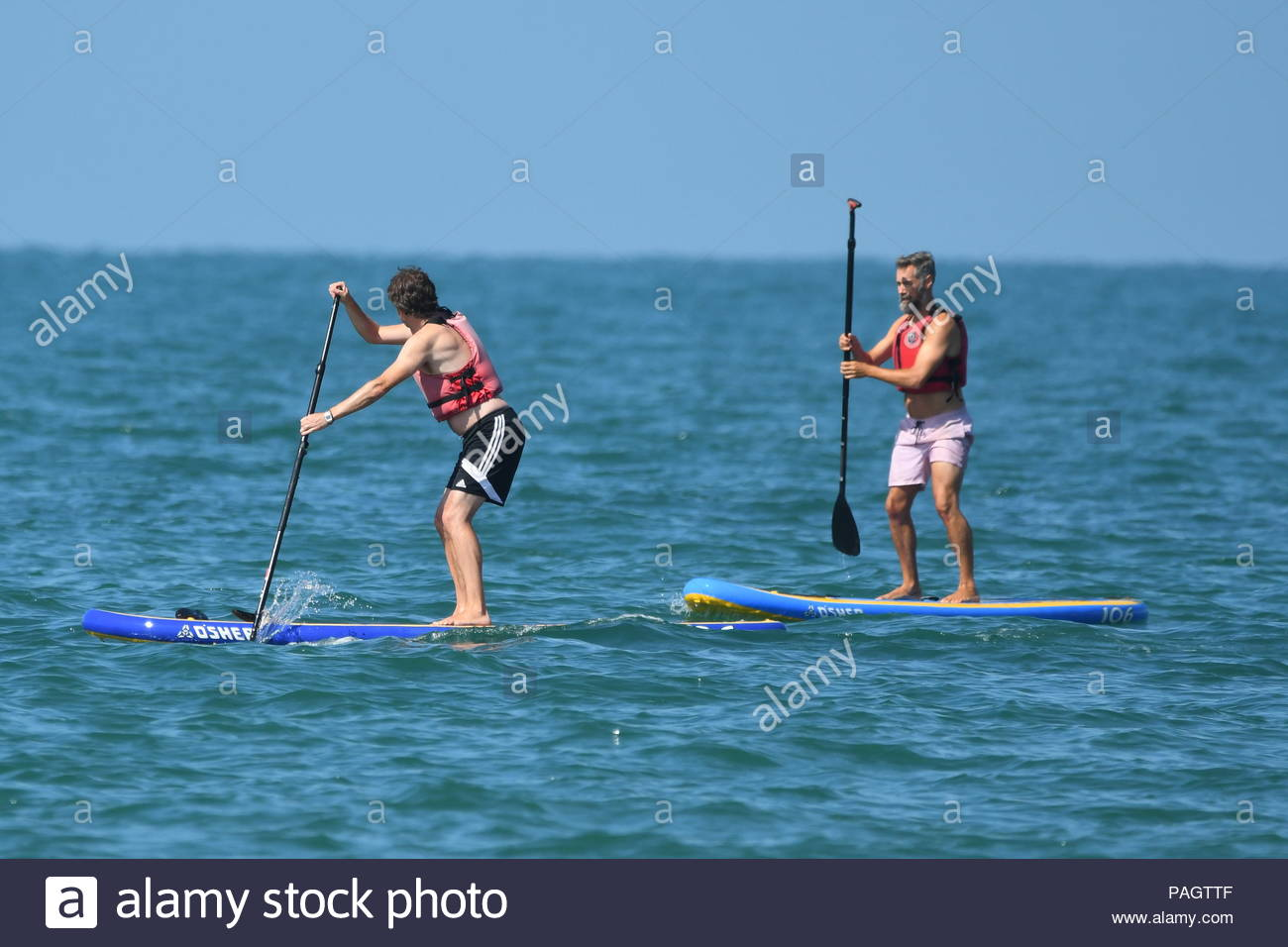 A couple of people using paddleboards in the July 2018 heatwave in England, UK. Paddleboards. Paddle boards. Paddle board. Paddleboarding. Paddleboarders. - Stock Image