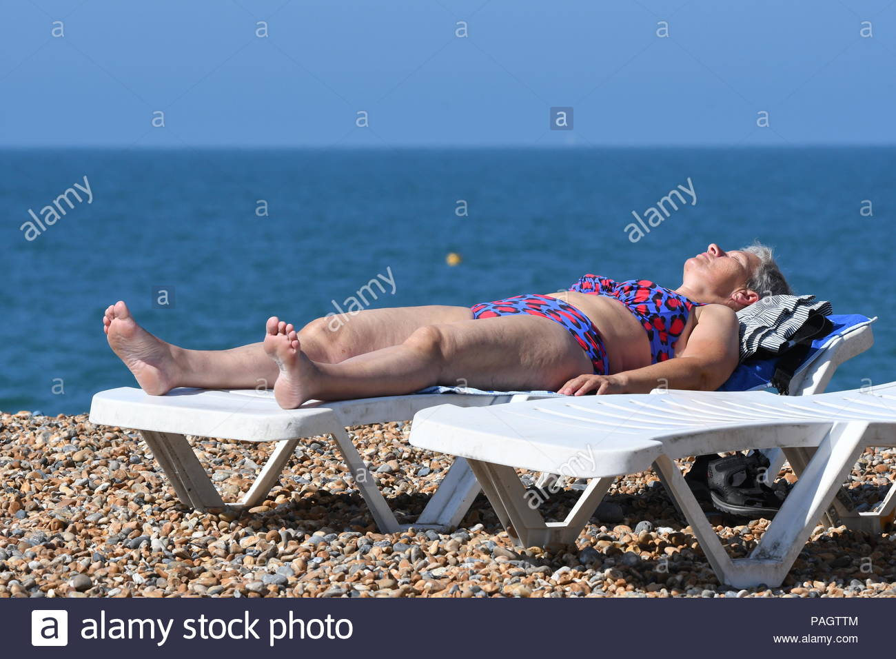 Brighton, East Sussex, UK. Monday 23rd July 2018. A woman sunbathes on the beach on another hot and sunny morning in Brighton. The temperature is expected to reach 24C today, reaching into the 30s by midweek. Credit: Geoff Smith / Alamy Live News Stock Photo