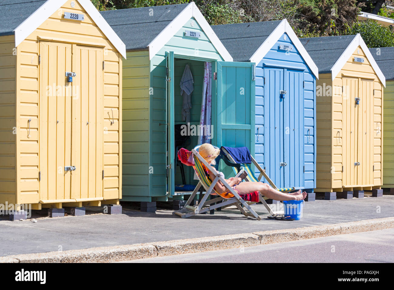 Bournemouth, Dorset, UK. 23rd July 2018. UK weather: the heatwave continues as temperatures rise on a scorching hot and sunny day at Bournemouth beaches with blue skies and unbroken sunshine. Sunseekers head to the seaside to soak up the sun. Woman sunbathing in deckchair reading a paperback book outside beach huts with feet up on bucket. Credit: Carolyn Jenkins/Alamy Live News - Stock Image