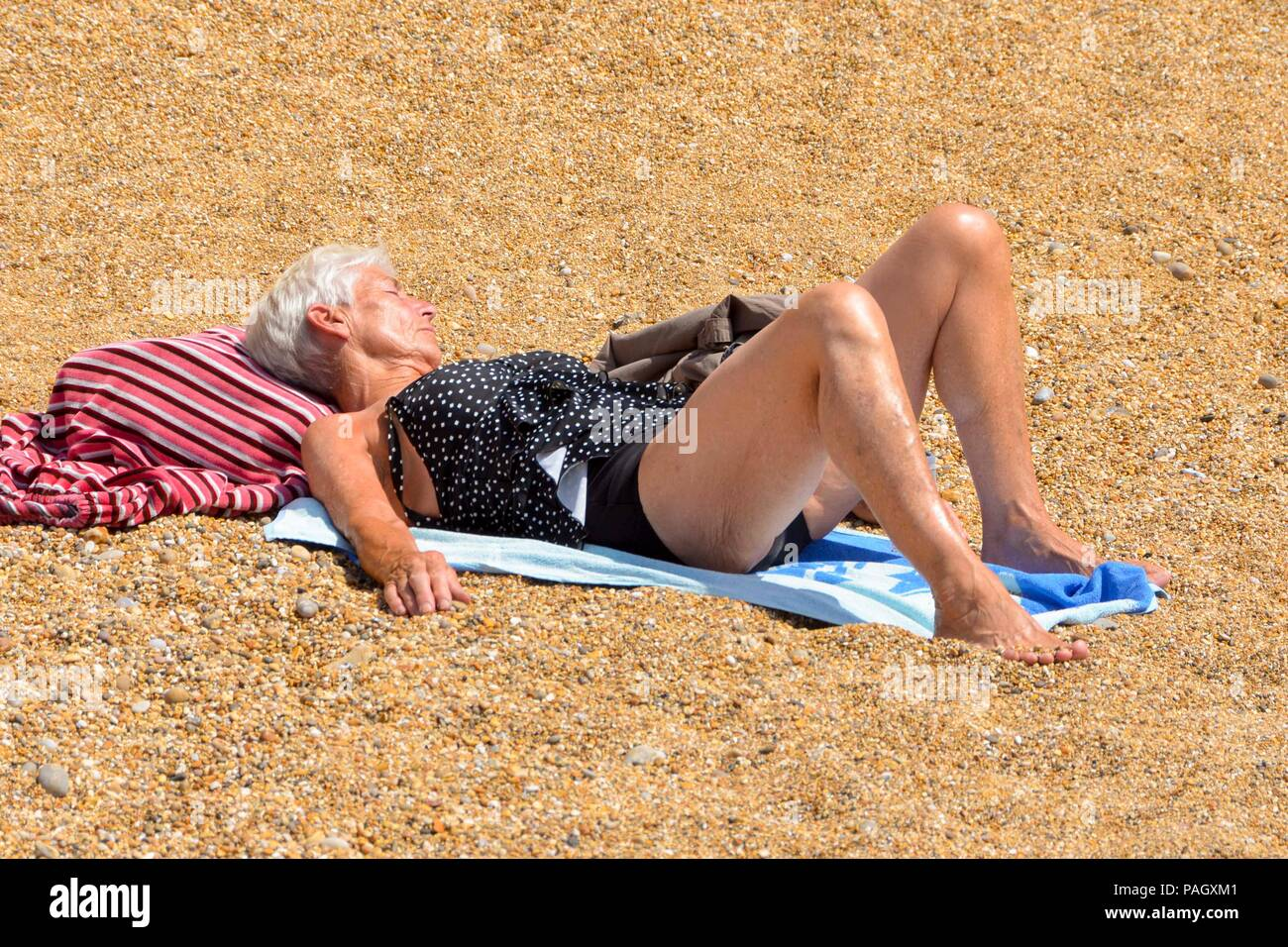 West Bay, Dorset, UK.  23rd July 2018. UK Weather.   A sunbather on the beach enjoying the hot sunshine at the seaside resort of West Bay in Dorset.  Picture Credit: Graham Hunt/Alamy Live News - Stock Image