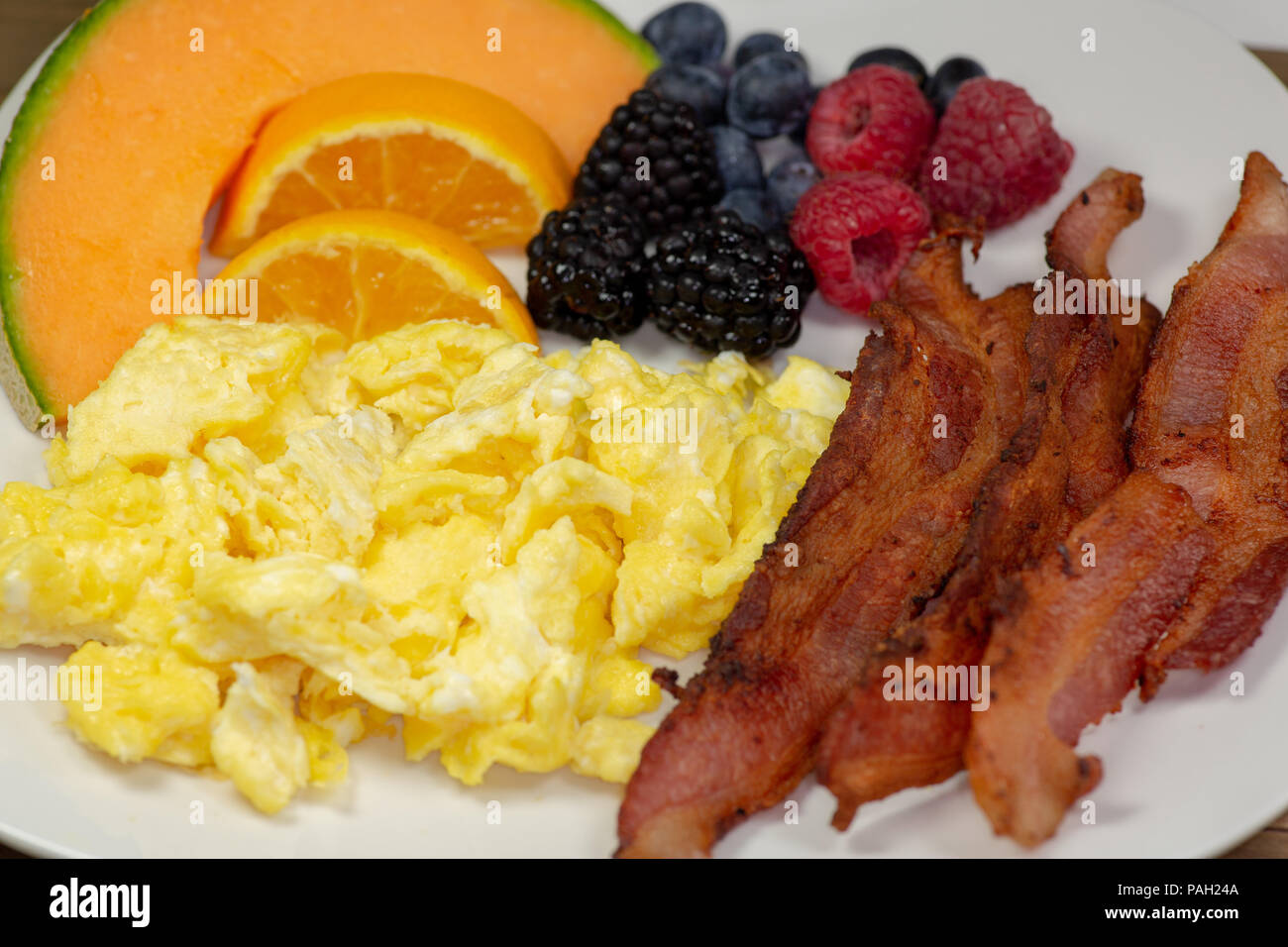 Breakfast plate of bacon, cantaloup slice, orange slices, blackberries, raspberries and blueberries on the kitchen table waiting to be eaten - Stock Image