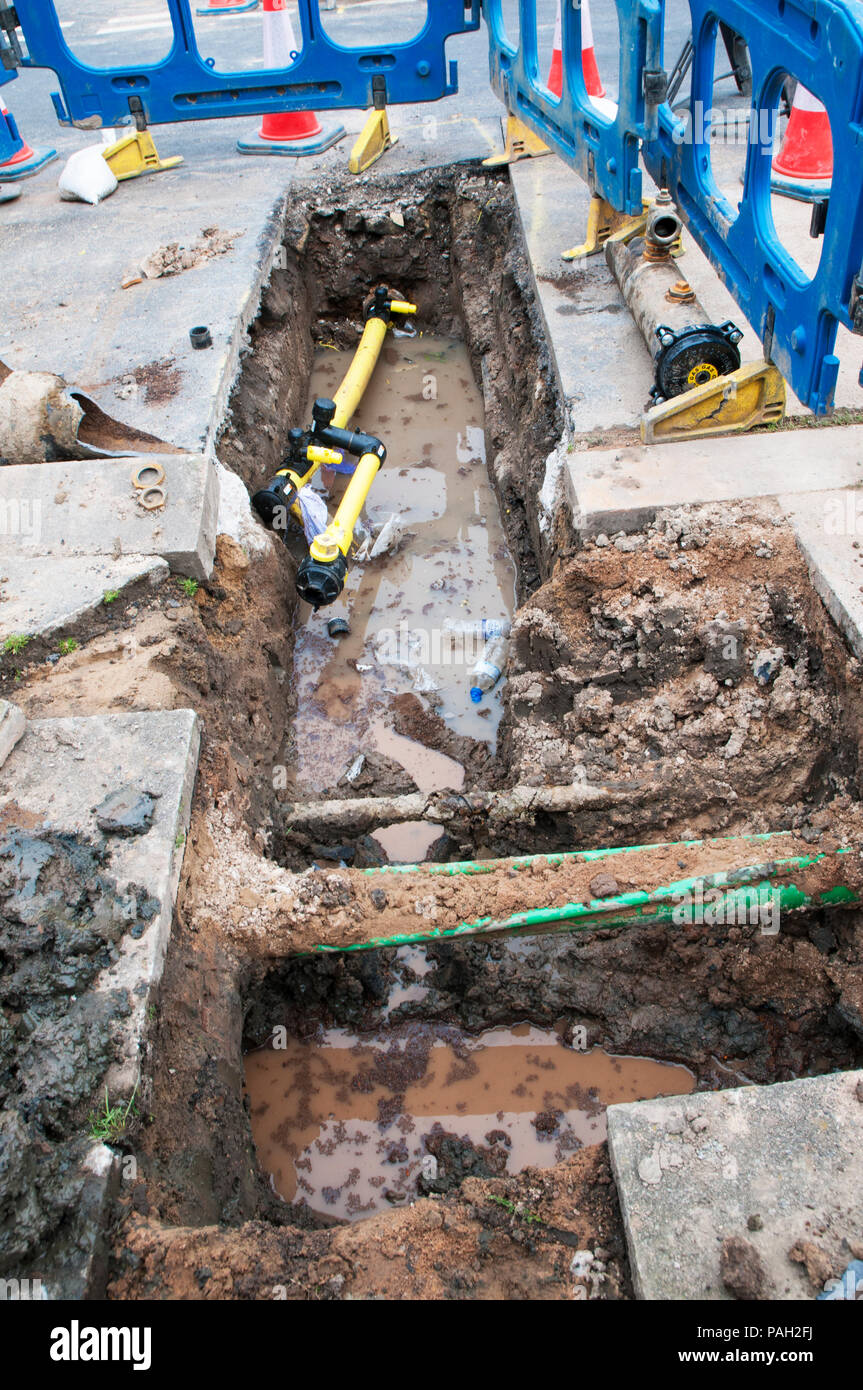 Roadway excavation to replace old cast iron gas main pipes.with plastic pipes. - Stock Image