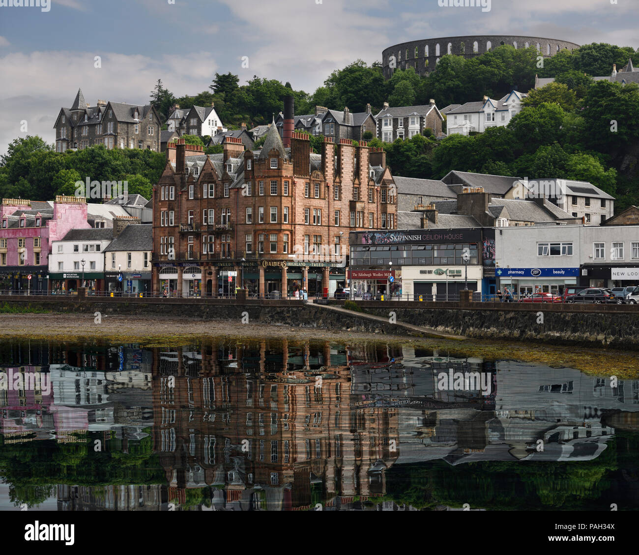 Historic buildings and McCaig's Tower on Battery Hill overlooking Oban harbour with water reflections in Oban Bay Scotland UK - Stock Image