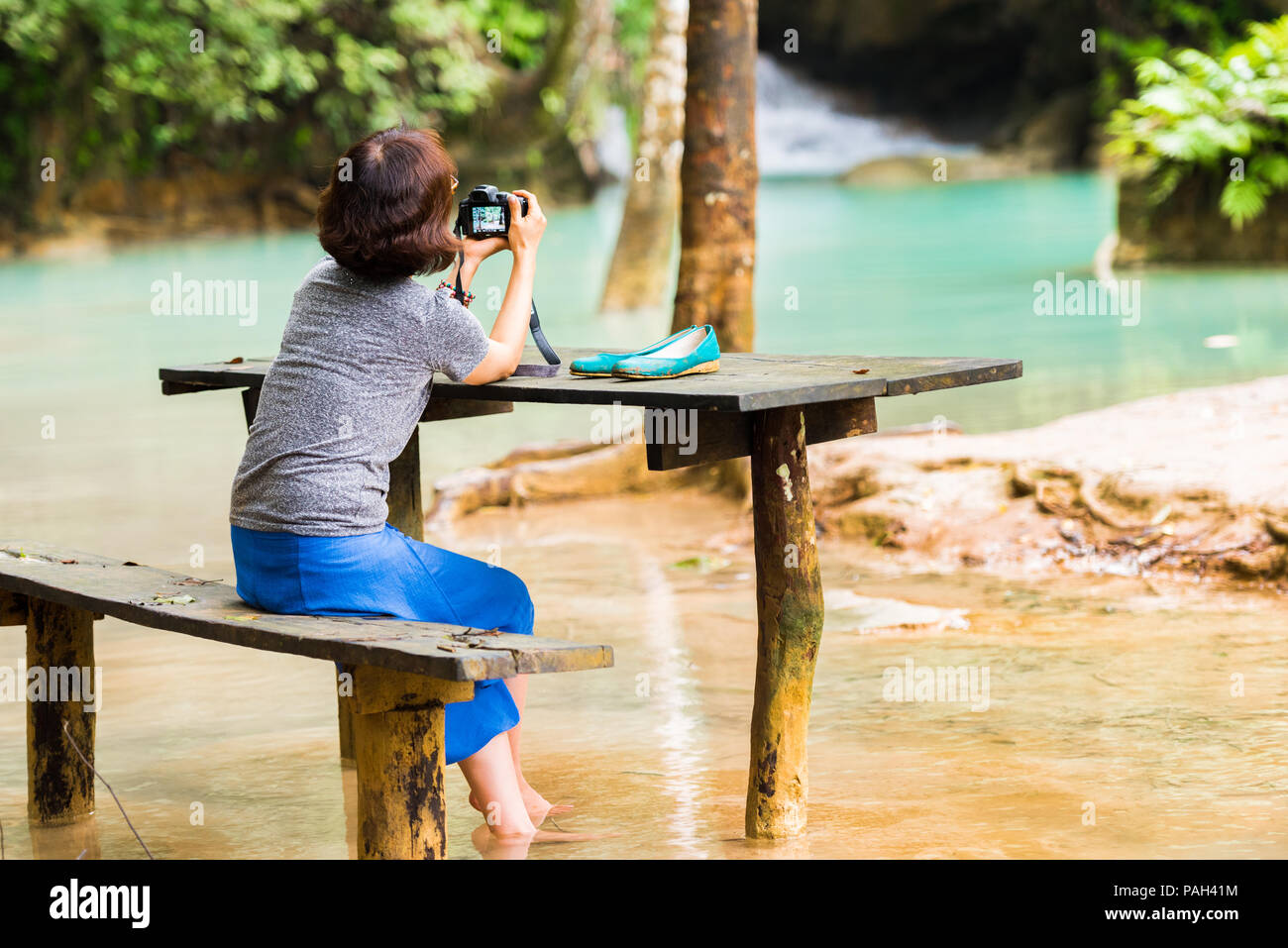 Woman near Kuang Xi Falls, waterfall in area mountain with forest, Luang Prabang, Laos. Copy space for text Stock Photo
