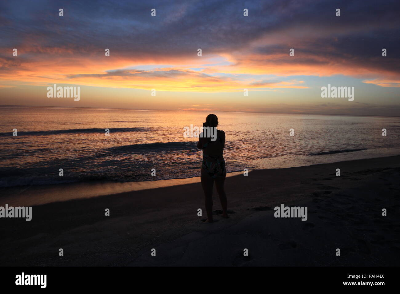Woman in silhouette photographing the sunset over the Gulf of Mexico on Captiva Island off Florida's west coast, United States. Stock Photo