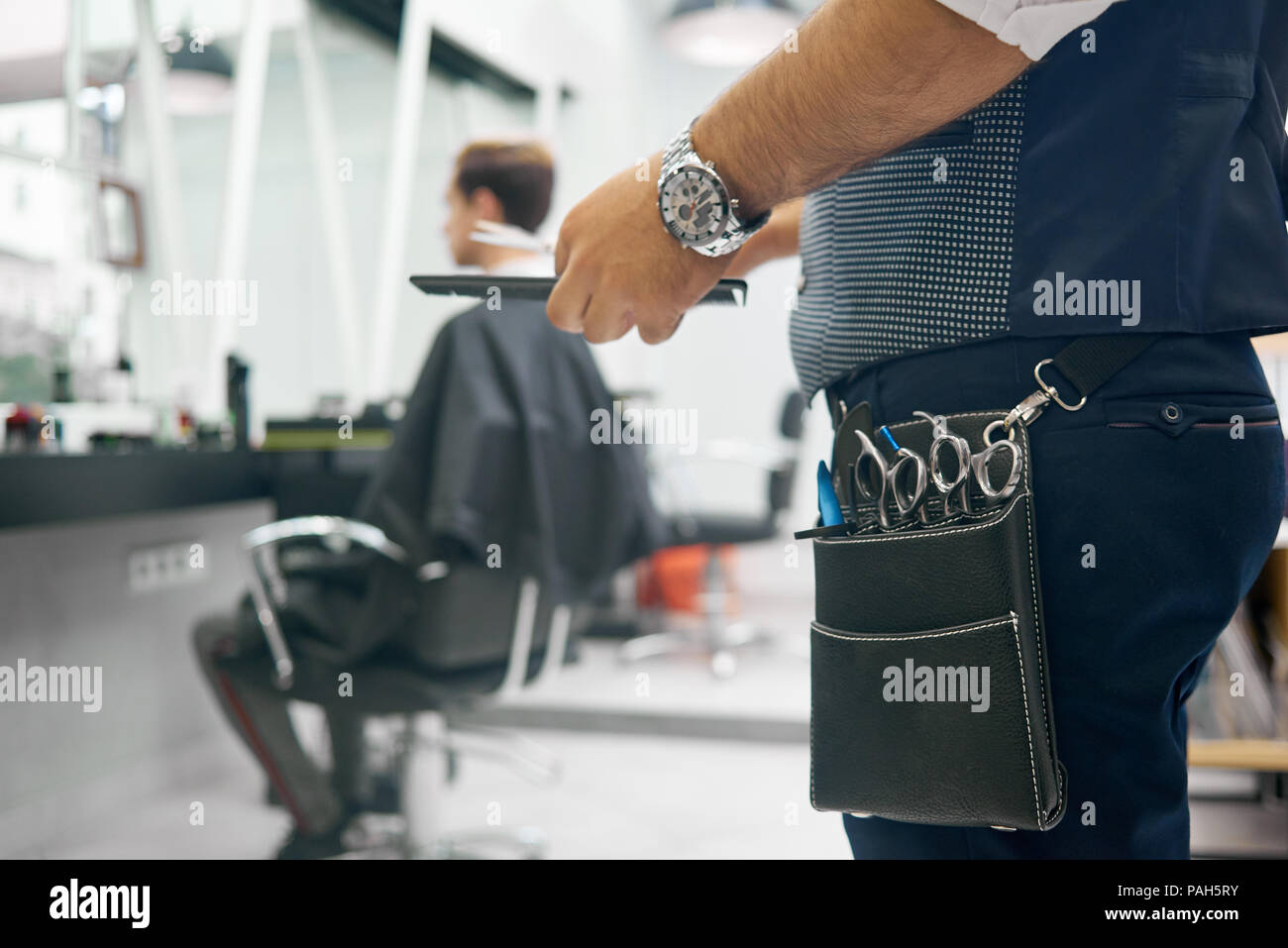 Close up of barber's leather bag with metallic sharp scissors for haircutting. Hairstyler wearing dark blue trousers, grey waistcoat, handwatch. Keeping black plastic comb. Client sitting behind. - Stock Image