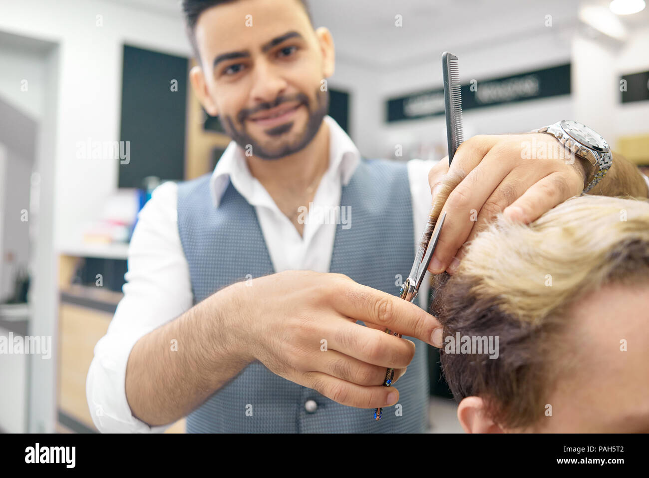 Doing new hairstyle for male model using sharp metallic scissors. Hairdresser wearing classic white shirt, grey waistcoat. Smiling, looking at camera, loving his job. Male model having toned hair. - Stock Image