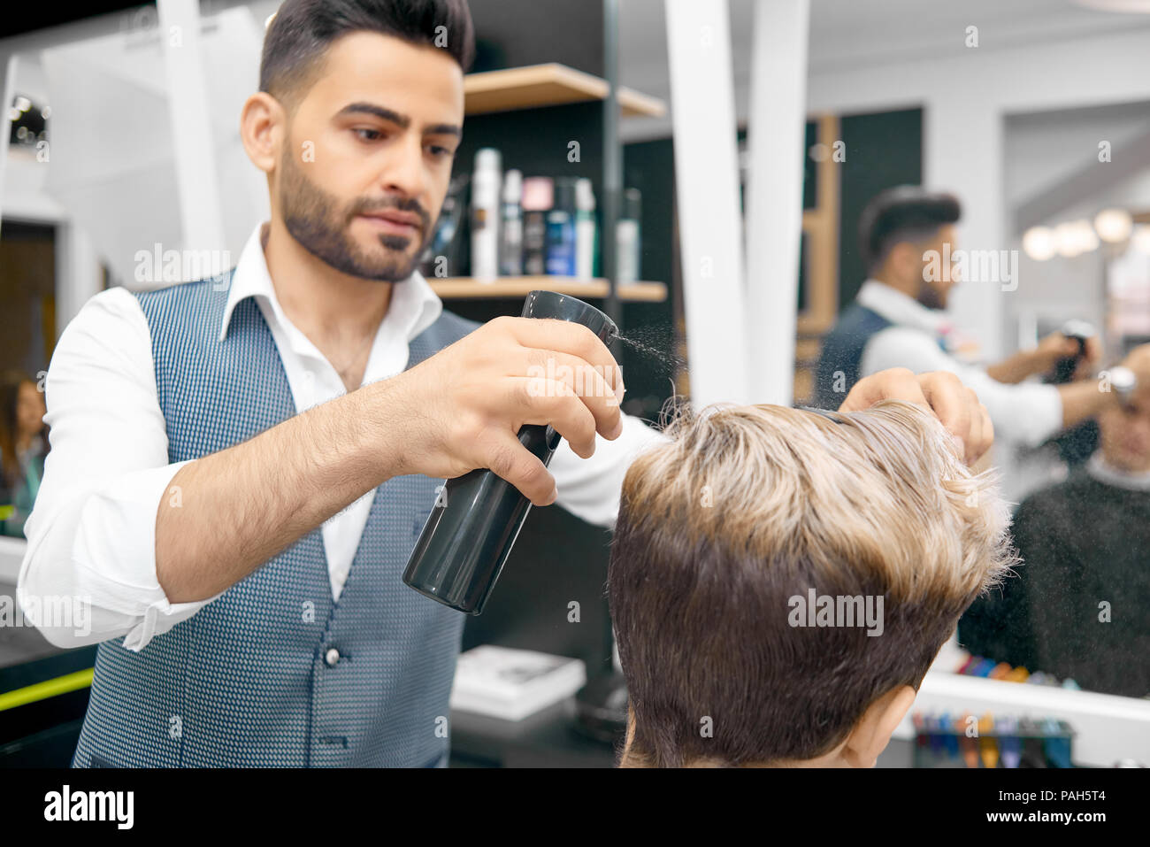 Doing new hairstyle for male model using hard fixation hairspray. Hairdresser wearing classic white shirt, grey waistcoat. Working in front mirror in beaty salon. Hair care products on background. - Stock Image