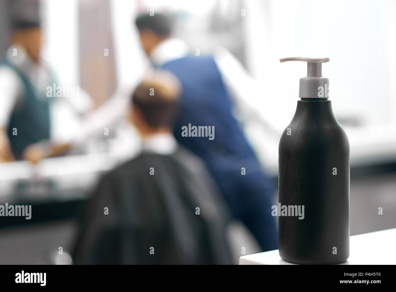 Photo of black plastic bottle with dispenser including hair care product. Standing on white glance surface in barber shop, beaty salon. Hairdresser working with client near mirror on background. - Stock Image
