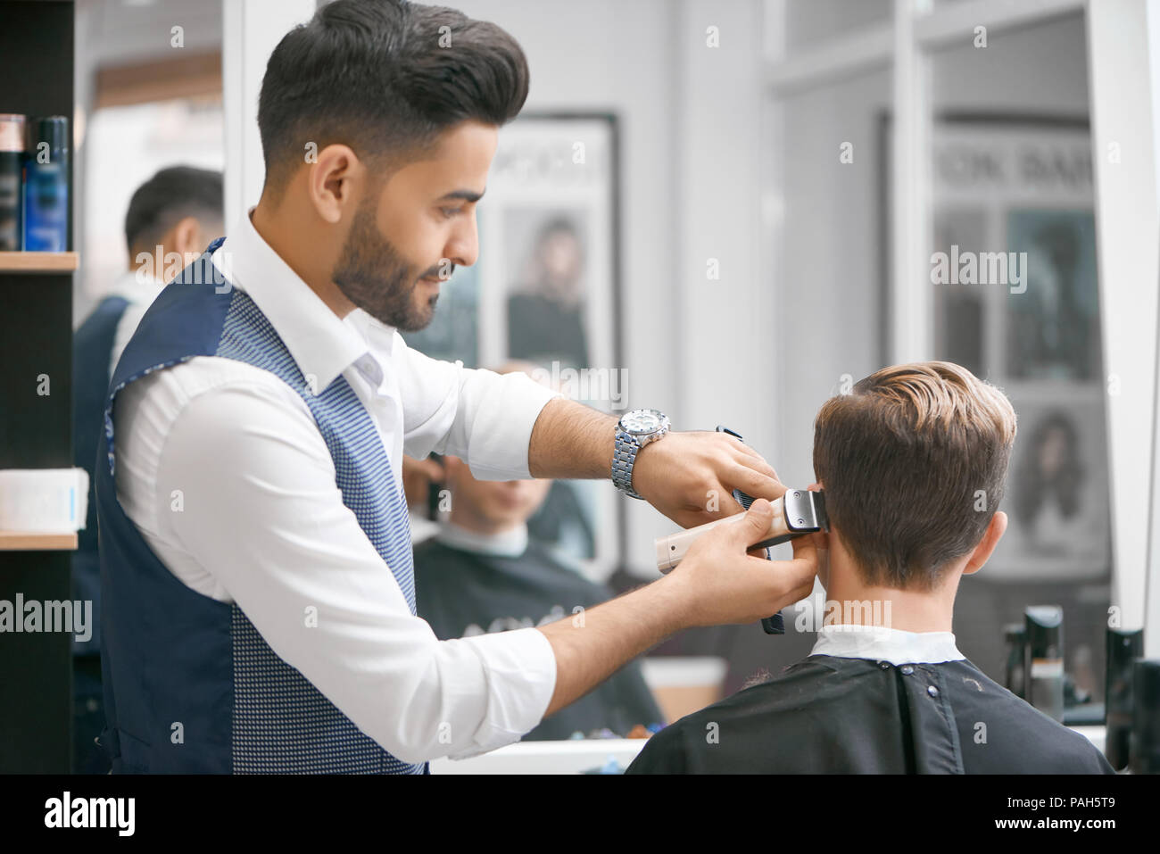 Barber doing new haircut for young client sitting in front of mirror. Wearing white casual shirt, grey waistcoat, watch. Looking concentrated, loving his job. Model covered with special black cape. - Stock Image