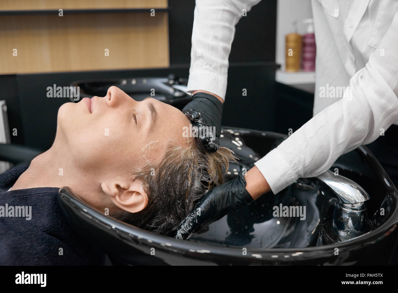 Hairstylist washing client's hair in a beaty salon's sink. Client sitting with his head laying in the black ceramic sink with closed eyes. Feeling good, relaxing. Hairdresser wearing black gloves. - Stock Image