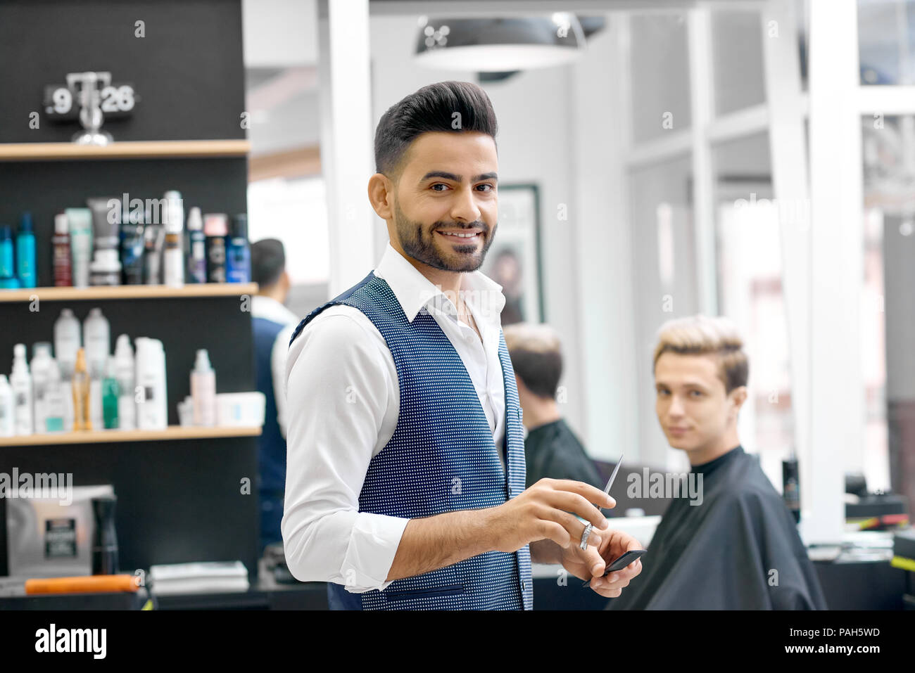 Smiling barber standing near client sitting near mirror, looking at camera. Wearing casual white shirt, stylish grey waistcoat. Posing in front of shelves with hair care products. Feeling positive. - Stock Image