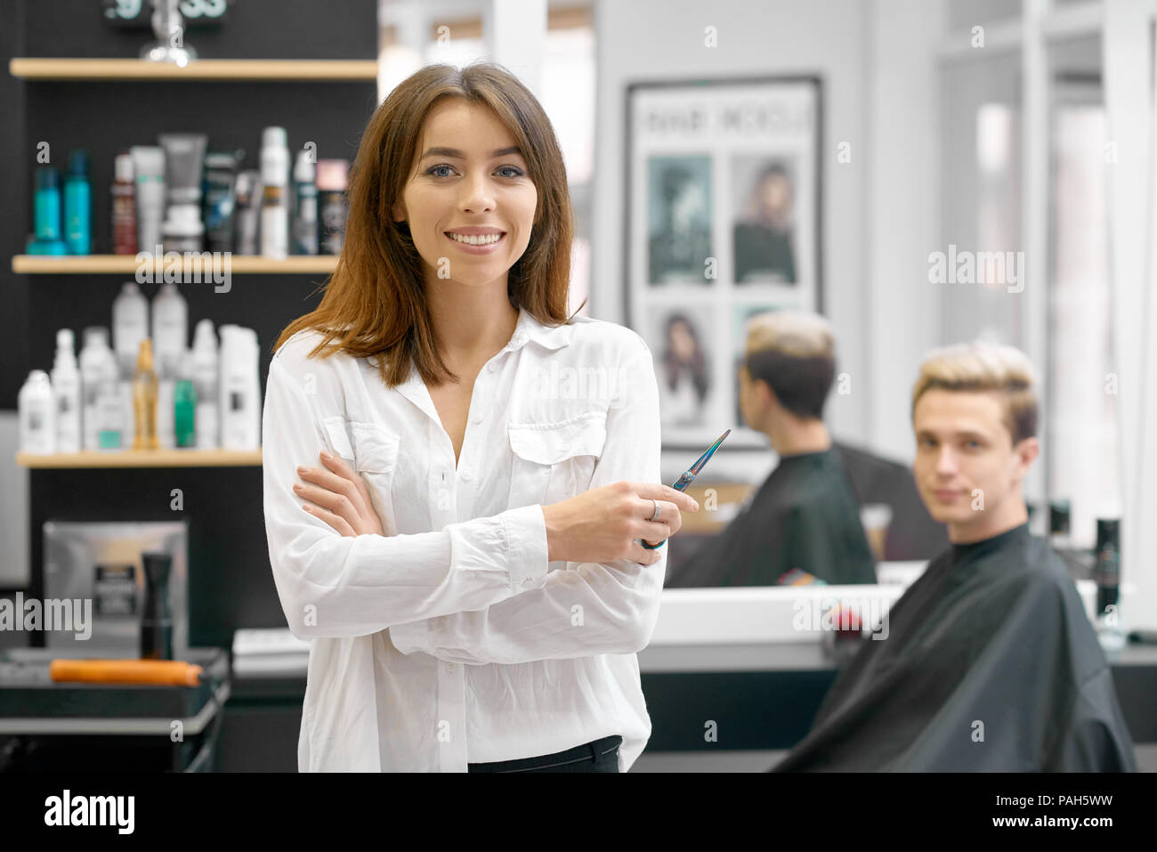 Female hairdresser posing in front of young male client sitting near big mirror and shelves with hair care products. Hairstyler wearing white casual shirt and looking at camera, smiling. - Stock Image