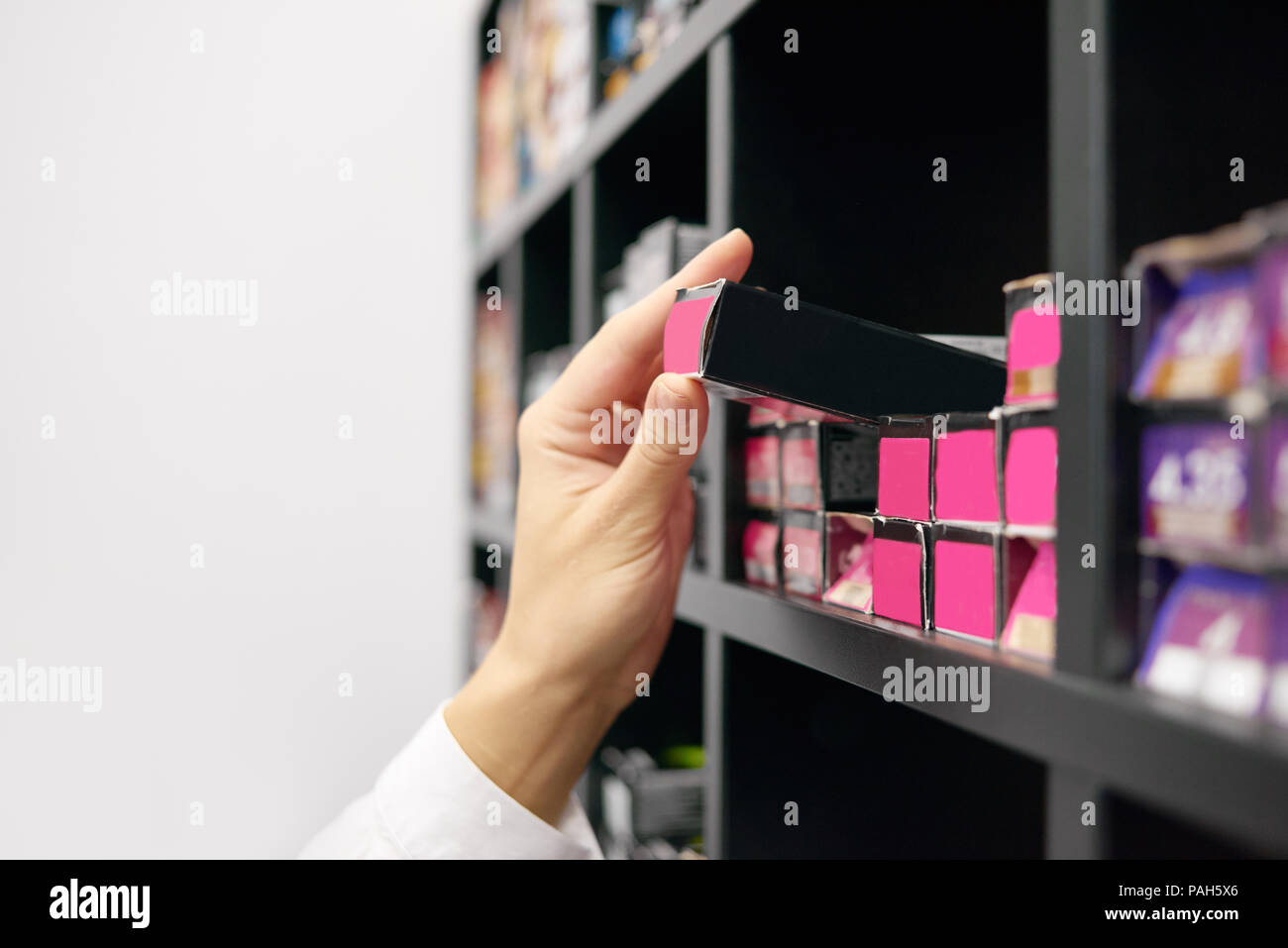 Client choosing hair care products in beaty salon. Little black boxes, packages with bright saturated pink etiquettes laying on wooden shelves on white background. Stock Photo