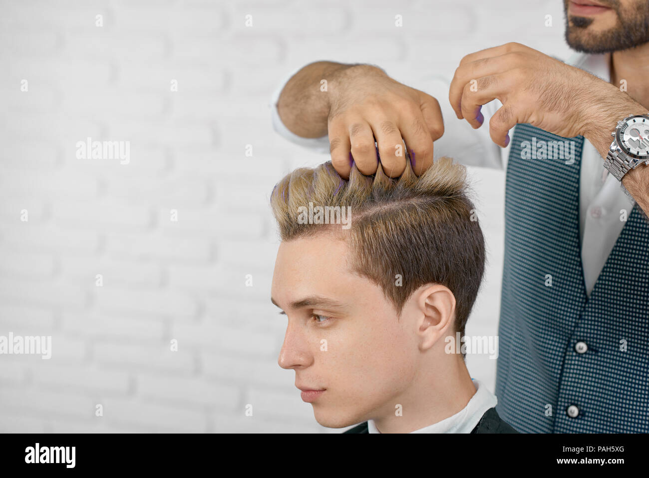 Photo of hair coloring in lilac color process. Hairdresser applying colorful tint on model's hair, working on white brick studio background. Hairstylist wearing white shirt and grey waistcoat. - Stock Image
