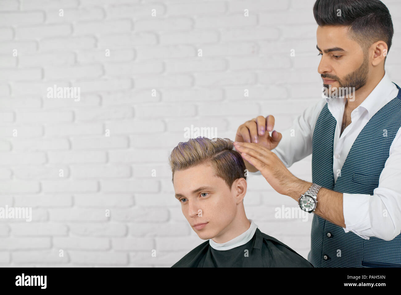 Barber doing lilac hair coloring for young handsome client. Hairdresser wearing grey waistcoat, white shirt, watch. Boy's clothes covered with special black cape. Sitting on white studio background. - Stock Image