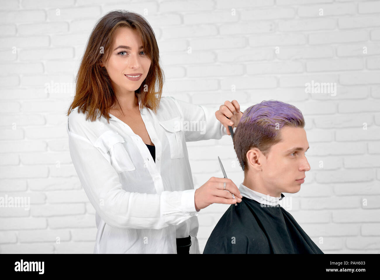 Female hairstylist doing haircut for young client with toned in violet color hair. Hairdresser using sharp metallic scissors and black plestic comb. Master wearing white shirt and looking at camera. - Stock Image