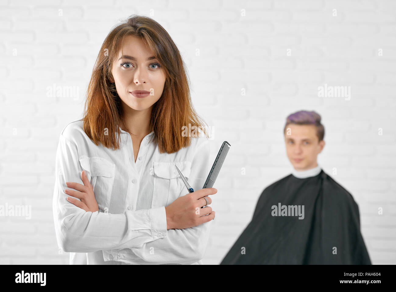 Female hairstylist standing in front of young client with toned lilac hair, covered with black cape. Woman wearing white classic casual shirt with pockets. Looking at camera, white background. - Stock Image