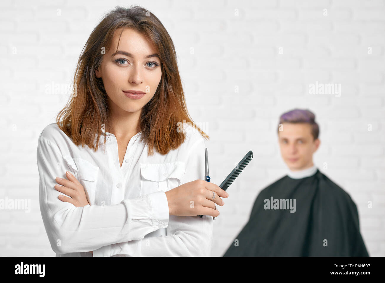Woman hairstylist looking at camera holdingblack plastic comb and sharp metallic scissors. Looking at camera wearing stylish white shirt. Young client with toned lilac hair sitting behind. - Stock Image